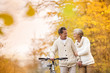 Senior couple with bicycle in autumn park - 73289012