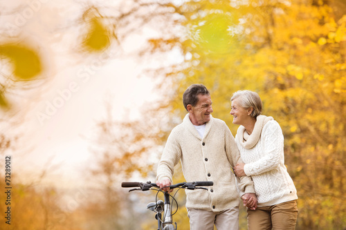 Plexiglas Wielersport Senior couple with bicycle in autumn park