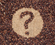 Red rice forming a question mark on burlap fabric