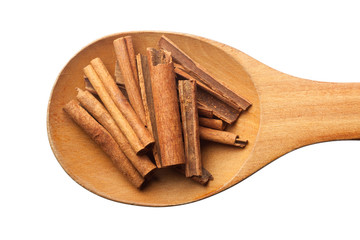 Wooden spoon with cinnamon isolated