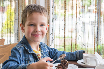 Boy in the cafe eating a delicious cake with nuts and chocolate