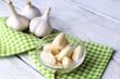 Fresh sliced garlic in glass bowl on wooden background