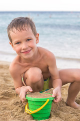 Little boy on the seashore playing with sand