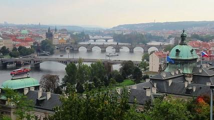 Prague view, river ships, bridges transport vehicles, flags wave