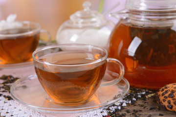 Teapot and cups of tea on table on light background