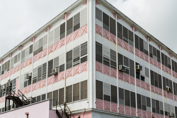 Old Pink and White Building with Window Air Conditioners