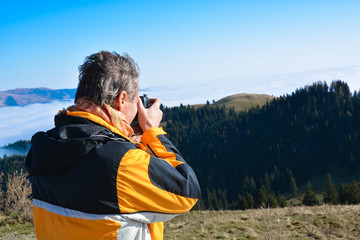Photographer man taking picture with photo camera on landscape