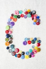 Letter G of the alphabet of buttons of various shapes and colors