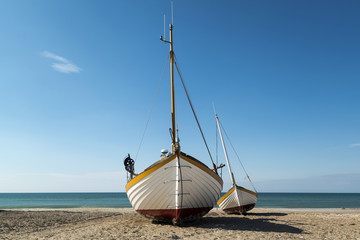 Two small fishing boats on the seashore