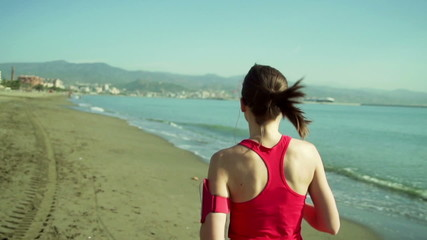 Young woman running on the city beach slow motion, shot at 120fp
