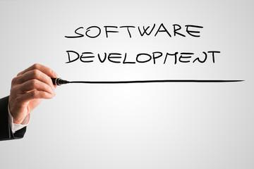 Hand of a man writing Software development on a virtual screen