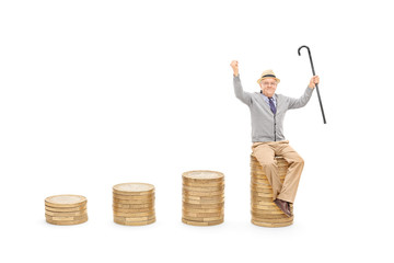 Joyful senior holding cane seated on pile of coins