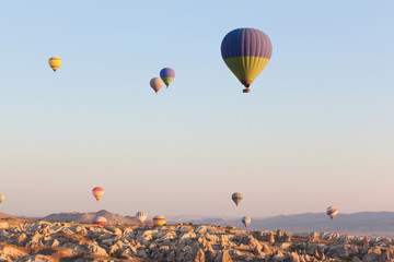 Multicolored balloons in flying in sky, sunrise time