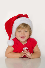 girl in costume of Santa at table and smiling
