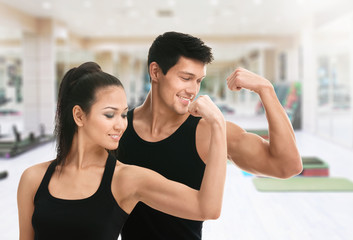 Two sportive trainers showing their biceps in gym