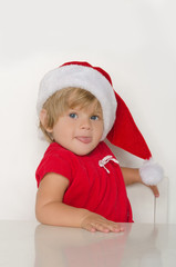 Child dressed as Santa Claus at table