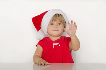 happy little girl in costume of Santa at table