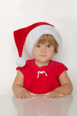 little girl in costume of Santa Claus at table