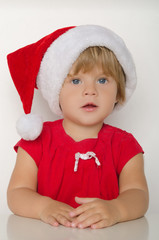 Surprised  girl in costume of Santa Claus at table