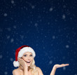 Beautiful woman in Christmas cap gestures palm up