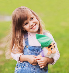 Little girl on the meadow holding a toy