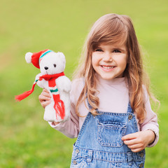 Happy little girl showing a toy