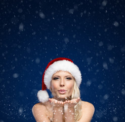 Attractive woman in Christmas cap blows kiss