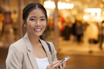 Young Woman and smart phone walking on street