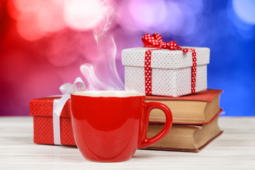 Steaming coffee cup with books and gift boxes