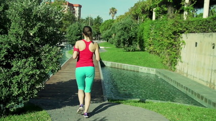 Beautiful woman running in city park slow motion, shot at 120fps