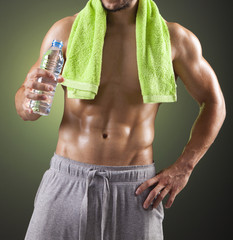 Fitness man holding a bottle of fresh water on black background