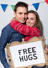 Couple with Free Hugs sign at a hipster party