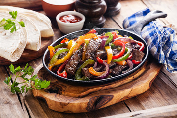 Beef Fajitas with colorful bell peppers in pan and tortilla brea