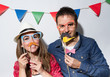 Leinwanddruck Bild - Young couple in a Photo Booth party with garland decoration