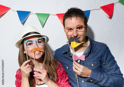 Leinwanddruck Bild Young couple in a Photo Booth party with garland decoration