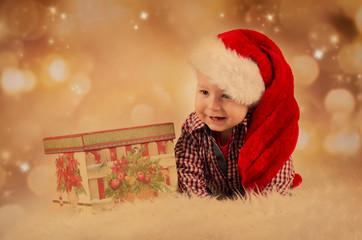 Lachendes Baby mit Geschenk und Nikolausmütze
