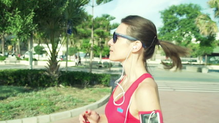 Beautiful female jogger running in the city on a sunny day slow