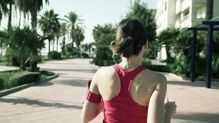 Young woman jogging in the city on a sunny morning slow motion