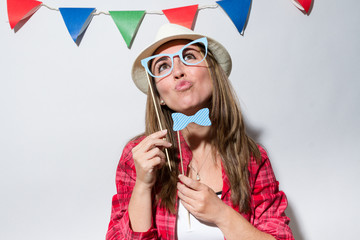 Woman in a Photo Booth party holding glasses and bow tie