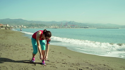 Young, beautiful woman tying shoelaces during jogging on the bea