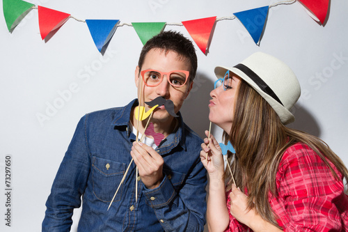 Couple in a Photo Booth party with garland decoration - 73297650