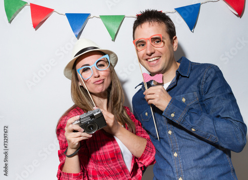 Hipster young couple in a Photo Booth party - 73297672