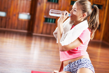 Young sporty girl taking a break and drinking water.