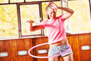 Girl spinning hula hoop, indoor.