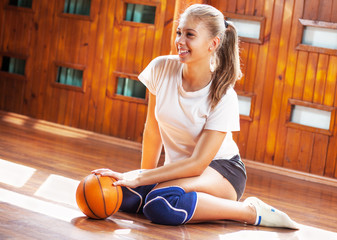 Sporty teenage girl posing and holding the ball
