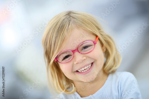 canvas print picture Cute blond little girl with pink eyeglasses
