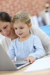 Mother and little girl using laptop computer