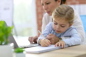 Woman working from home while daughter is drawing