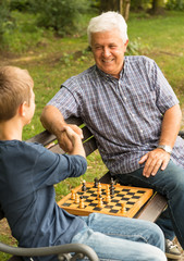 Grandfather and grandson playing chess in the park