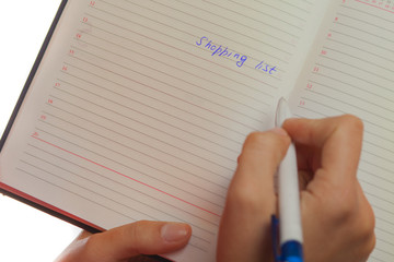 Image of female hand with pen holding shopping list